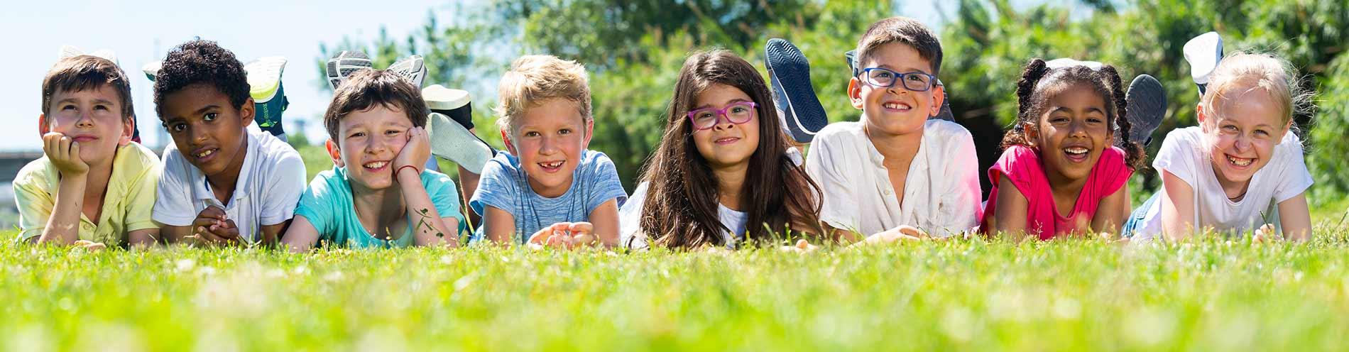 Kinderland Egglkofen - Kinder liegen fröhlich auf der Wiese