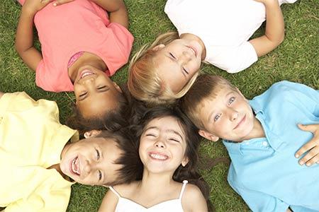 Hortkinder liegen im Gras