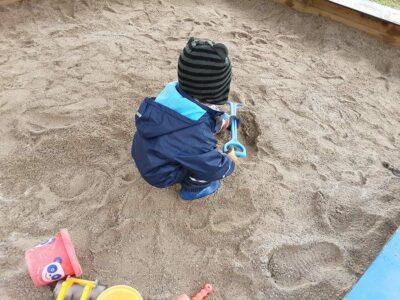 Krippenkind spielt im Sand