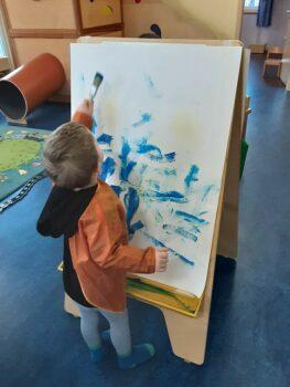 Krippe: Kind malt auf Leinwand